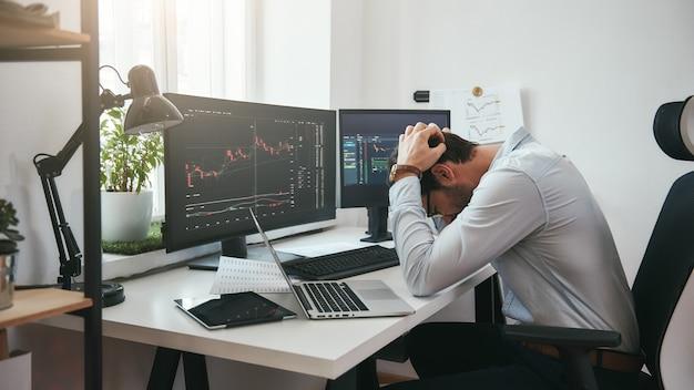 Чувство грусти в депрессии молодой бизнесмен или торговец в формальной одежде, держа голову в руках во время работы