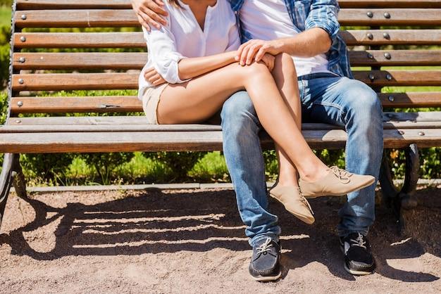 Чувствует себя в безопасности рядом с ним. крупным планом влюбленная пара, сидящая на скамейке