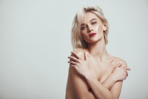 Чувство сексуальной красивой и стройной женщины со светлыми волосами, прикрывающими грудь руками