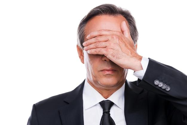 Чувство стыда. портрет зрелого мужчины в строгой одежде, закрывающего глаза рукой, стоя на белом фоне
