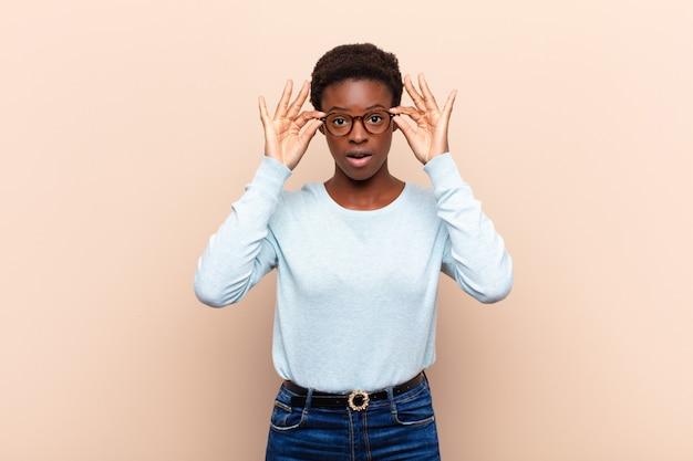 ショックを受け、驚いて、驚いて、驚いた、信じられないような表情でメガネを握っている