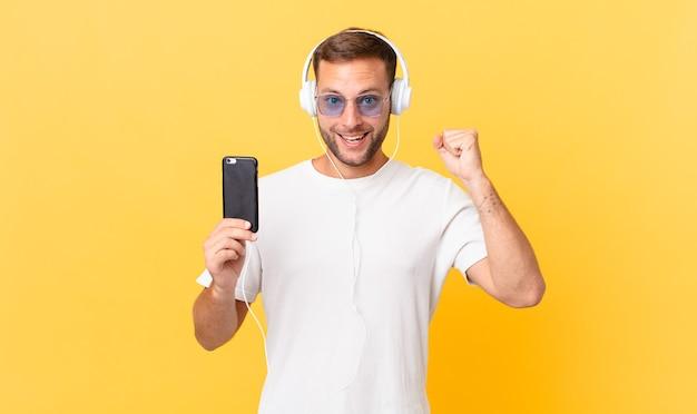 충격을 받고 웃고 성공을 축하하며 헤드폰과 스마트폰으로 음악을 들으며
