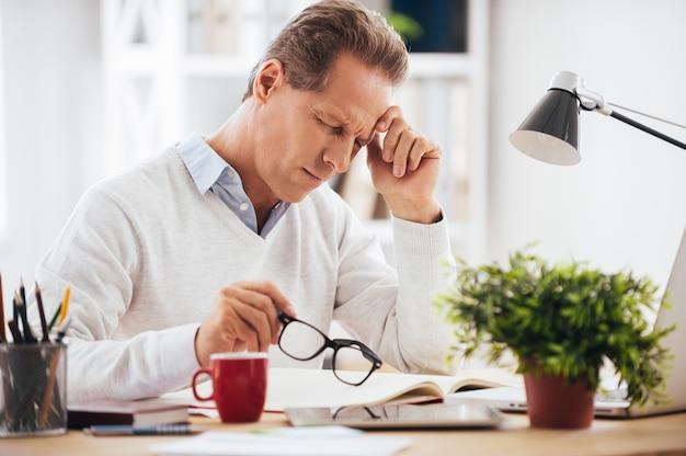 気分が悪くて疲れている。彼の職場に座って、彼の眼鏡を手に持っている間、疲れ果てているように見える欲求不満の成熟した男