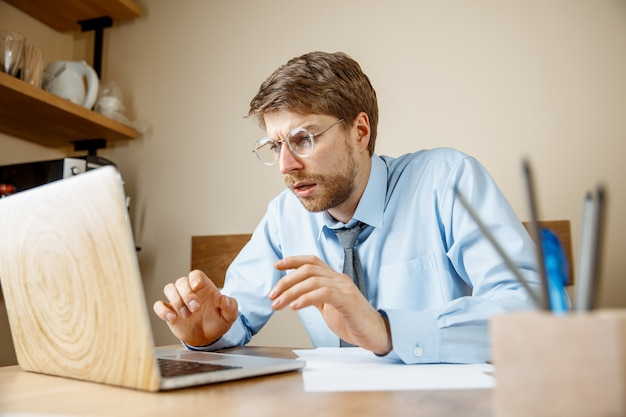 아프고 피곤함. 사무실에서 그의 작업 장소에 앉아있는 동안 그의 머리를 마사지 좌절 슬픈 불행 아픈 젊은 남자. 계절 독감, 유행성 인플루엔자, 질병 예방 개념