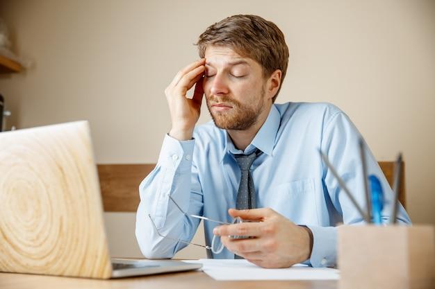 気分が悪くて疲れている。オフィスの彼の職場に座っている間彼の頭をマッサージする欲求不満の悲しい不幸な病気の若い男。季節性インフルエンザ、パンデミックインフルエンザ、疾病予防の概念