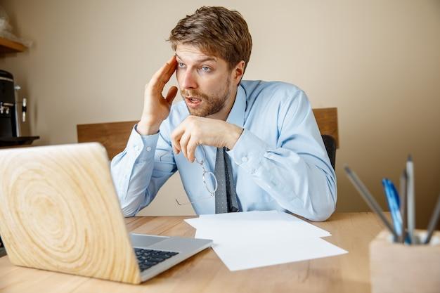 Чувство усталости и тошноты. разочарованный, грустный несчастный больной молодой человек массирует голову, сидя на своем рабочем месте в офисе.