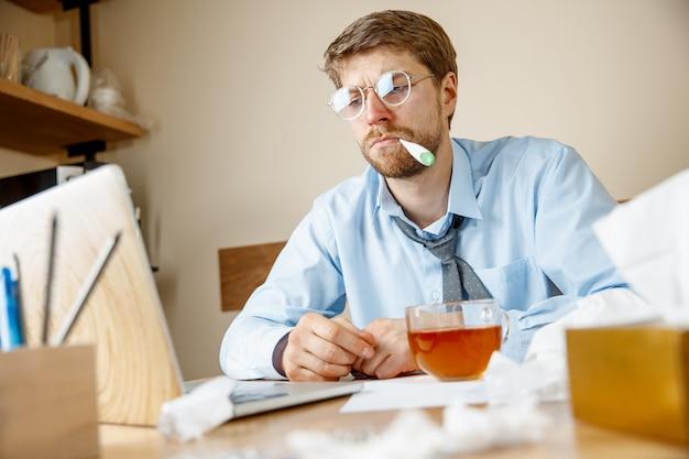 気分が悪くて疲れている。オフィスで働いている熱いお茶を飲んでいる男性、ビジネスマンは風邪の季節性インフルエンザにかかりました。パンデミックインフルエンザ、病気の予防、オフィスの空調は病気を引き起こします
