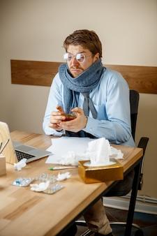 아프고 피곤함. 사무실에서 일하는 뜨거운 차 한잔을 가진 남자, 사업가 감기, 계절 독감에 걸렸습니다. 유행성 인플루엔자, 질병 예방, 사무실의 에어컨이 질병을 유발합니다.