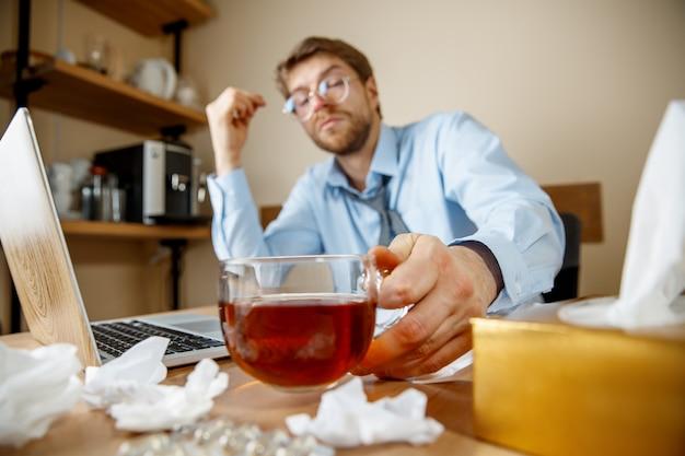 Чувство усталости и тошноты. человек с чашкой горячего чая, работающий в офисе