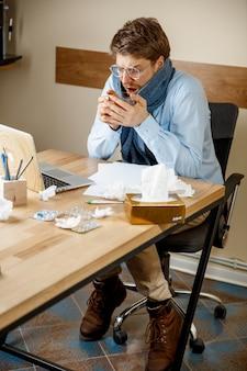 気分が悪くて疲れている。オフィスで働いている熱いお茶のカップを持つ男