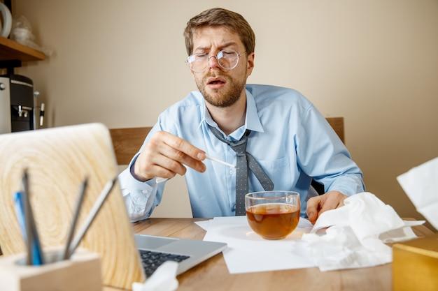 Sensazione di malessere e stanchezza. l'uomo con una tazza di tè caldo che lavora in ufficio, uomo d'affari preso raffreddore, influenza stagionale. influenza pandemica, prevenzione delle malattie, aria condizionata in ufficio causano la malattia