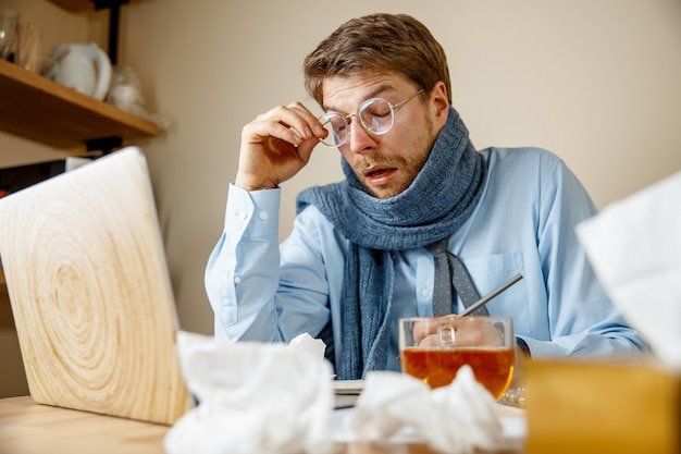Feeling sick and tired. the man with cup of hot tea working in office, businessman caught cold, seasonal flu. pandemic influenza, disease prevention, air conditioning in office cause sickness