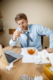 Sensazione di malessere e stanchezza. l'uomo con una tazza di tè caldo che lavora in ufficio, uomo d'affari preso raffreddore, influenza stagionale. l'influenza pandemica, la prevenzione delle malattie, l'aria condizionata in ufficio causano la malattia