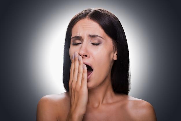 Сонный. портрет скучающей молодой женщины без рубашки, прикрывающей рот рукой и зевая, стоя на сером фоне