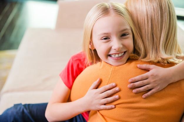 Чувствую себя таким счастливым рядом с мамой. счастливая мать и дочь обнимаются, сидя на диване вместе