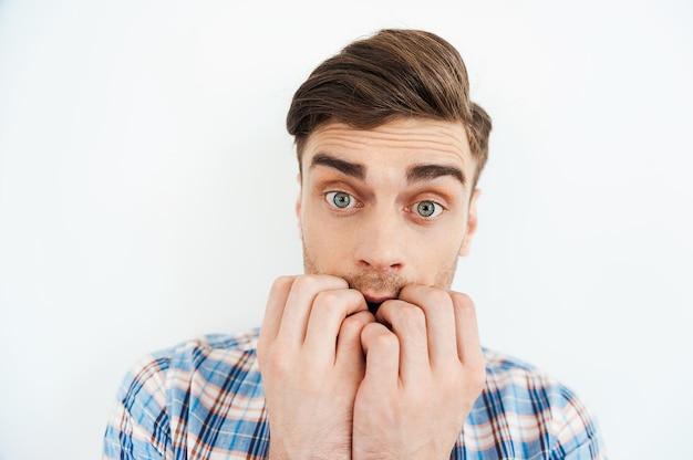 Мне так страшно. нервный молодой человек кусает ногти и смотрит в камеру