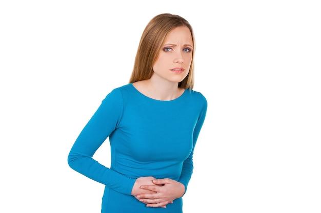 Ощущение боли в животе. разочарованная молодая женщина, держащая руки на животе и смотрящая в камеру, стоя изолированной на белом