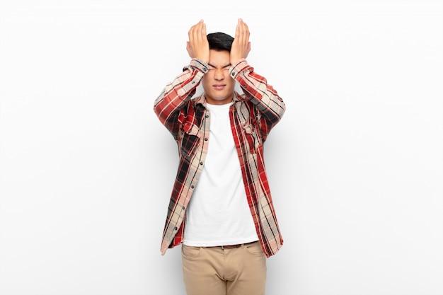 Чувство стресса и тревоги, депрессии и разочарования от головной боли, поднимая обе руки к голове