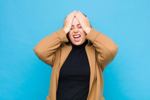 ストレスと不安、落ち込んで頭痛で欲求不満を感じ、両手を頭に上げている