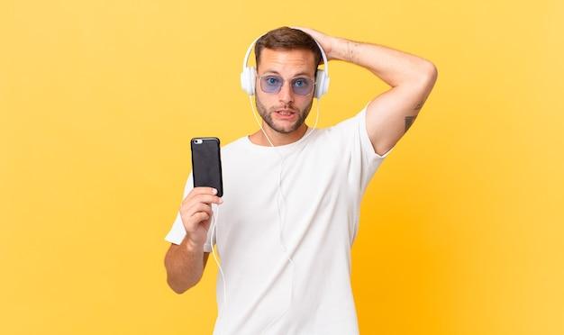 ストレス、不安、恐怖を感じ、手を頭に置き、ヘッドフォンとスマートフォンで音楽を聴く