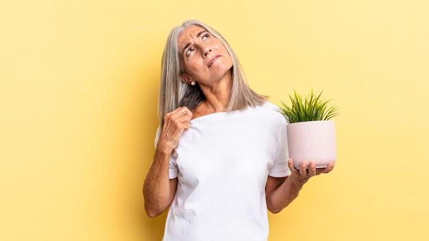 ストレスを感じ、不安になり、疲れて欲求不満になり、シャツの首を引っ張って、装飾用植物を保持するのに問題があることに不満を感じている