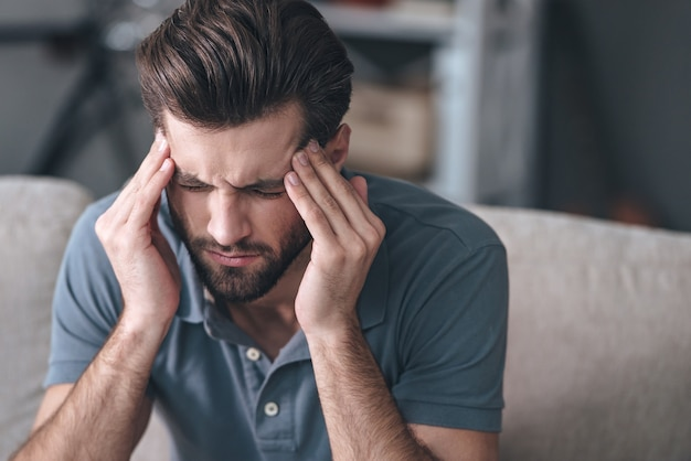 스트레스를 느낀다. 집에 있는 소파에 앉아 머리를 만지고 눈을 감고 있는 좌절된 잘생긴 청년