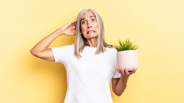 ストレス、心配、不安、恐怖を感じ、手を頭に置き、装飾用植物を持って誤ってパニックに陥る