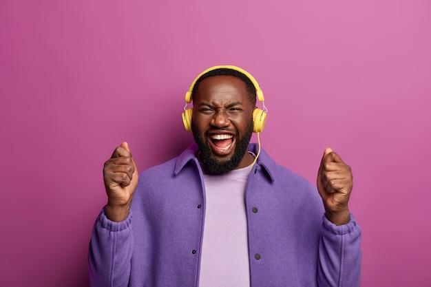 成功を感じています。ポジティブな無精ひげを生やした男は、拳を上げて立って、楽しく笑い、余暇の間にヘッドフォンでお気に入りの曲を聴きます