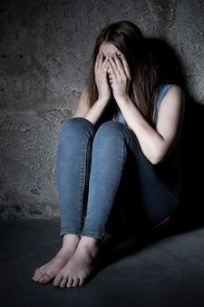 겁에 질린 느낌. 어두운 방에서 바닥에 앉아 있는 동안 손으로 얼굴을 덮고 충격을 받은 젊은 여성