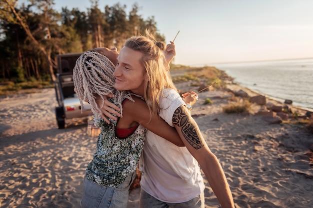 ありがたい気持ち。完璧な週末に感謝している彼女のハンサムな男を抱き締める白いドレッドヘアを持つ女性