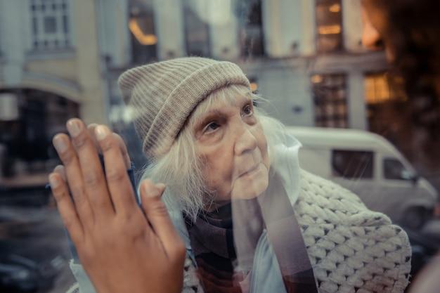 つながりを感じる。接続を感じながら窓に置かれている女性の手のクローズアップ