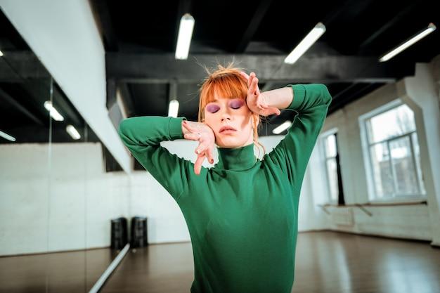Чувствуя танец. молодая рыжеволосая учительница танцев с ярким макияжем, вдохновленная танцами в студии