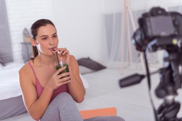 喉が渇いた。魅力的な楽しいアスレチック黒髪の若い女性が座ってブログのビデオを作っている間、笑顔でフレッシュジュースを飲んでいます