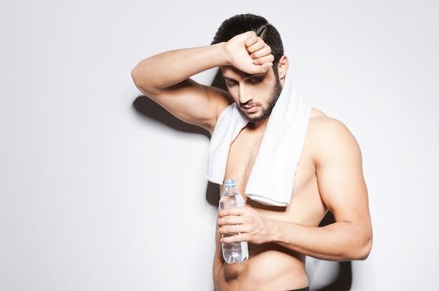운동 후 피로감. 회색 배경에 서서 물병을 들고 눈을 감고 있는 근육질의 젊은 남자