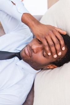 피곤하고 우울한 느낌. 셔츠와 넥타이에 좌절된 아프리카 남자의 상위 뷰
