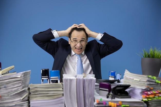 피곤하고 과로 사업가가 서류가 가득한 사무실 책상에서 비즈니스 스트레스에 우울한 그의 머리를 잡았다. 프리미엄 사진