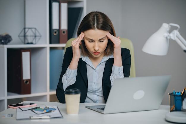 疲れやストレスを感じています。欲求不満な若い女性が目を閉じて鼻をマッサージしながら、オフィスの職場に座っています。