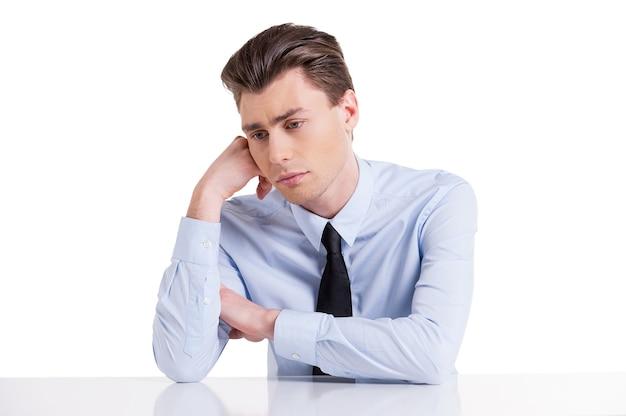 Чувство усталости. подавленный молодой человек в рубашке и галстуке, держа голову за руку и глядя в сторону, сидя за столом и изолированным на белом