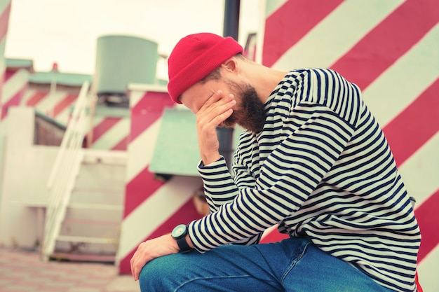 Feeling tired. exhausted young man wearing striped clothes and closing his eyes while sitting alone