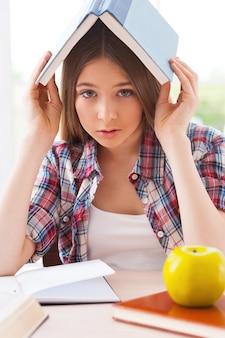 Чувство усталости от учебы. разочарованная девочка-подросток несет книгу на голове и смотрит в камеру, сидя за столом с лежащими на ней книгами