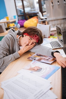 Feeling tired. student feeling exhausted while doing a lot of homework at the end of the semester