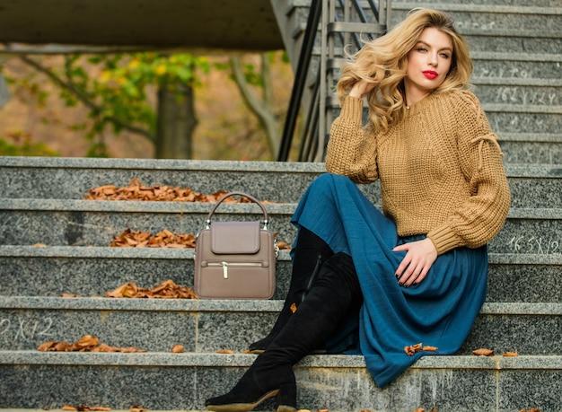 Чувство модности. осень женщина вьющиеся волосы на открытом воздухе. студент повседневного стиля. осень. женская красота. модель. девушка в гофрированной юбке и свитере. плиссированный тренд. девушка длинные светлые волосы по лестнице.