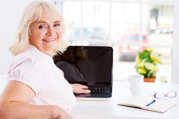 Ощущение молодости и полноты энергии. вид сзади жизнерадостной пожилой женщины, оглядывающейся через плечо и улыбающейся во время работы на ноутбуке