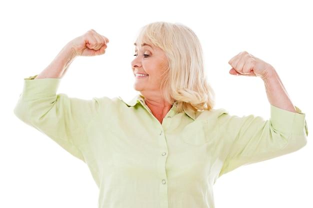 Ощущение молодости и здоровья. веселая старшая женщина проверяет ее бицепс и улыбается, стоя на белом фоне
