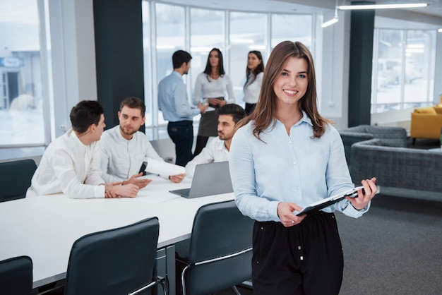 Feels good because she loves she's job. portrait of young girl stands in the office with employees at background