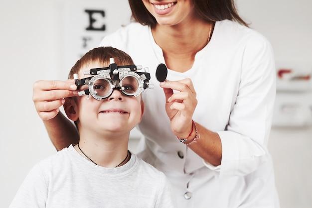 Приятно. ребенок сидит в кабинете врача и проверил его остроту зрения.