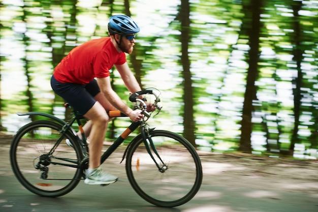 気持ちいい。自転車のサイクリストは晴れた日に森のアスファルト道路に