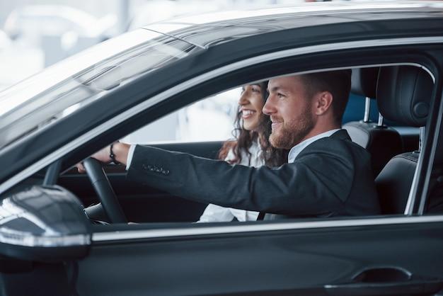 좋은 느낌. 자동차 살롱에서 새 차를 시도하는 사랑스러운 성공적인 부부