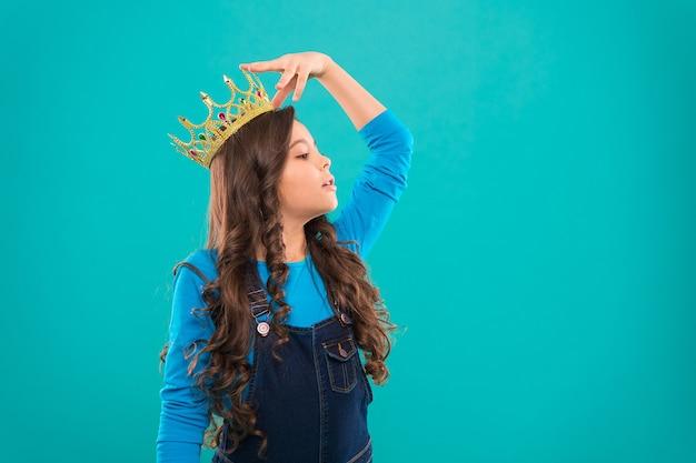 女王のように感じます。子供は王女の黄金の王冠のシンボルを着用します。王女になることを夢見ているすべての女の子。レディリトルプリンセス。青い背景に立っている間、女の子のかわいい赤ちゃんは王冠を着用します。子供の頃の概念。