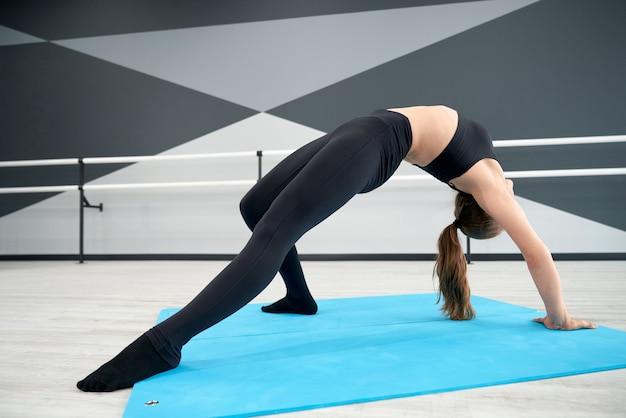 Feemale 십대 댄스 스튜디오에서 다리 위치 연습